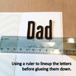 Using a ruler to line up the letters before gluing them down